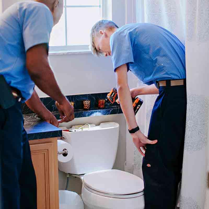 Plumber performing toilet repair service